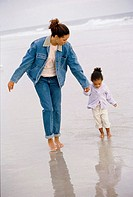 Mother and her daughter walking together at the beach