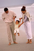 Father and mother walking with their daughter on the beach