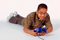 Portrait of a boy lying on the floor holding a game joystick