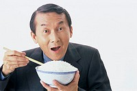 Portrait of man holding a bowl of rice