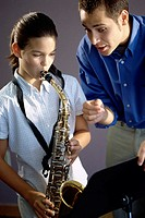 Man teaching a girl how to play the saxophone