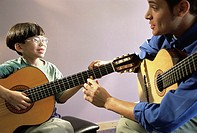 Man teaching a boy how to play the guitar