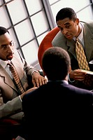 Three businessmen talking in a meeting