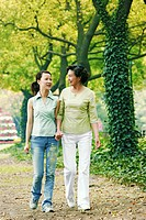 A mother and daughter holding hands walking in the park.