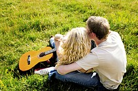 Top angle view of a couple sitting on the grass hugging