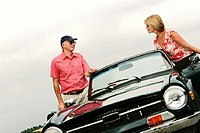 A married couple standing next to their roofless car talking