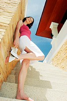A barefooted woman standing on the stairs holding her high heels