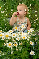 A young girl sitting in a garden sniffing flowers.