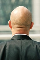 Back shot of a bald man in business suit.