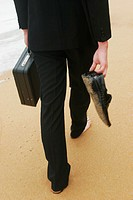 A waist-down shot of a lady walking barefeet on the beach holding a briefcase and her shoes.