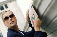 A woman in business suit and sunglasses reading a newspaper.