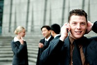 A man in business suit talking on the handphone.