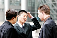 A man scratching his head while two other men watching.