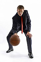 Man in business suit dribbling a basketball.