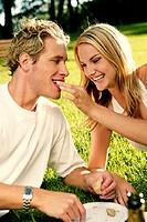 A woman feeding her boyfriend.