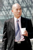 Bald man in business suit holding a cup.