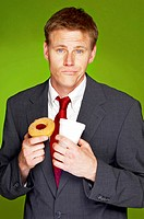Man in business suit holding a cup and a tart.