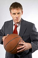 Man in business suit holding a basketball.