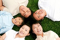 Top angle view of a family lying on the grass in circle.