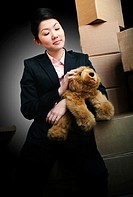 A lady in formal suit sitting on stacked boxes holding a furry bear.
