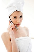 a woman with her hair and body wrapped up in towel talking on the handphone.