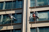 Window washers work at extreme heights to clean windows on tall buidings and skyscrapers in Chicago, Illinois. USA.
