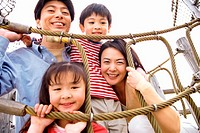 Portrait of a Family With Two Young Children on a Climbing Frame