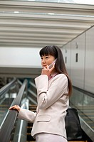 Businesswoman Standing on an Escalator Using a Mobile Phone