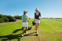 Two Women in Golfwear Walking and Pulling a Golfbag
