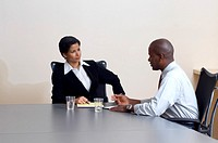 Businessman and Businesswoman Talking in a Meeting Room