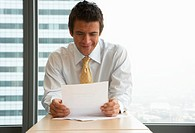Businessman at desk in office, holding document, smiling