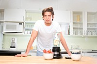Young man in kitchen by blender, portrait