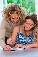 Mother helping daughter (13-15) writing in notebook, smiling