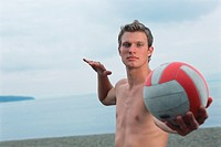 Young male volleyball player about to serve ball on beach, portrait