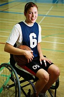 Young female basketball player in wheelchair, smiling, portrait