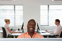 Businessman smiling, portrait, two people at computers in background