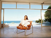Mature woman on chair indoors by ocean, portrait