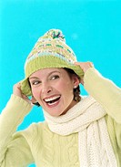 Woman pulling down wollen hat on head, smiling, close-up