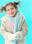 Girl (7-9) holding snow in gloved hands, smiling