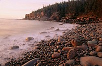 Ocean waves misty, in Maine, USA, smooth and flowing over rocks and Otter Cliffs in the background. Acadia National Park. Maine, USA