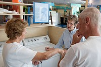 Salesperson Joy Hermann, center, talks about the Maytag dryer to shoppers Veronica and Richard Lanzon of Kirkwood. Missouri. USA.