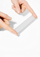Fingers holding ruler