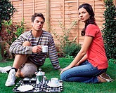 Young couple having coffee in the garden (thumbnail)