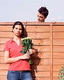 Man looking at woman over garden fence (thumbnail)