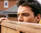Man looking over garden fence