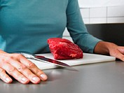 Woman with beef on chopping board