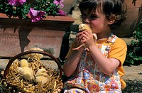 Young girl playing with chicks in a basket