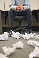 Man in Cubicle Strewn with Crumpled Paper