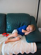 A three year old boy sleeps at home on a couch and with a little red car