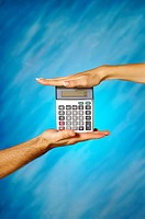 Close-up of a man and a woman's hands holding a calculator